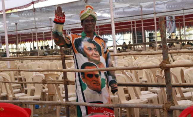 A supporter of Indias Congress party wearing photographs of India\'s former prime ministers...
