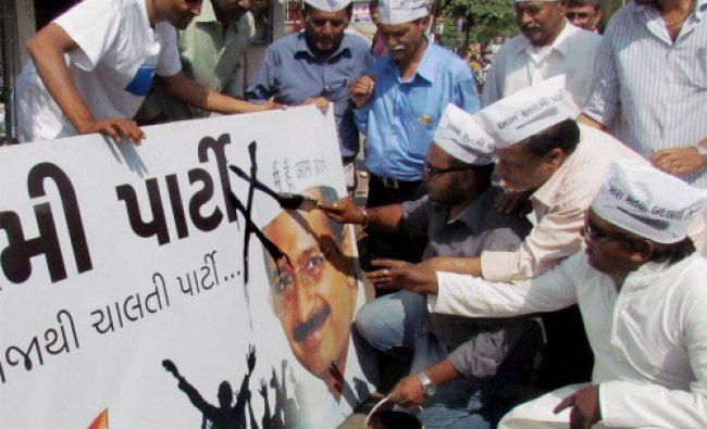 Activists of Hindu Navnirman Sena paint black color on a billboard of Aam Admi Party...