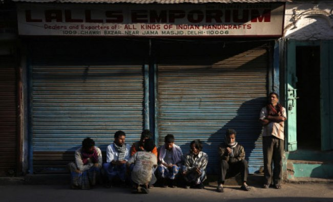 Men wait for business early morning at Chawri Bazar, in New Delhi...