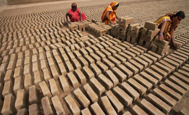 Women labourers make work at a brick factory on the eve of International Women\'s Day...