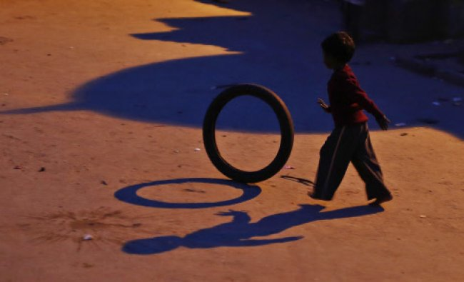 A boy plays with a tyre outside his home next to railway tracks in New Delhi...