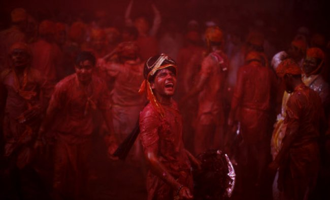 A man from the village of Nangaon teases men from Barsana as they play holi at the Ladali...