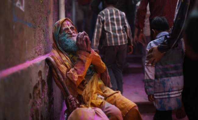 An elderly man seek alms from devotees outside the Ladali or Radha temple before...