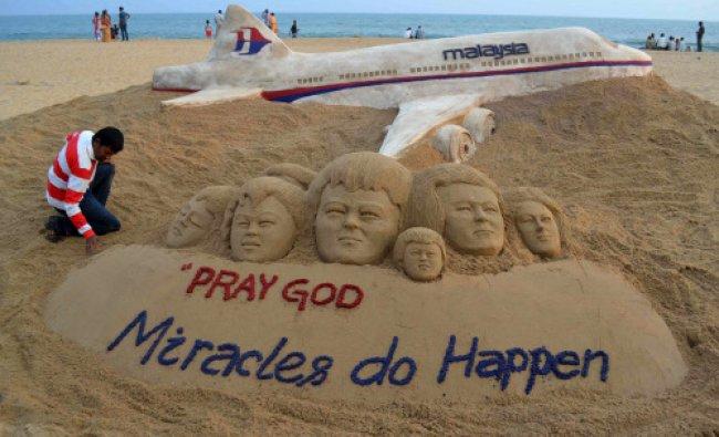 Sand artist Sudarshan Patnaik applies the final touches to a sand art sculpture he created...