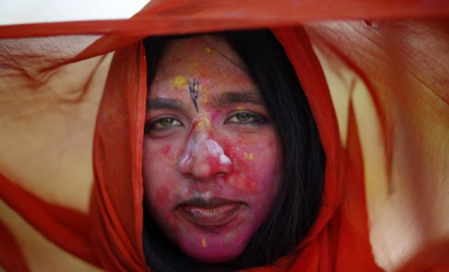 A devotee with her face daubed in colours looks on...