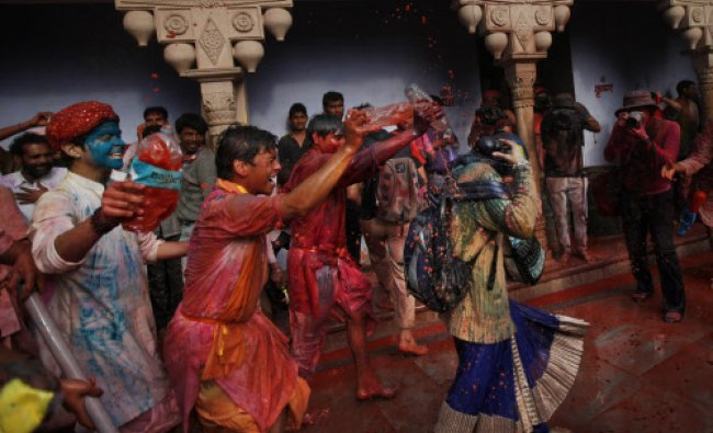 Boys throw colored water on a woman at the Nandagram Temple famous for Lord Krishna during ...