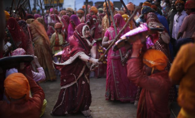 Women from Nandgaon village beat the shield of a man from Barsana village during Lathmar ...