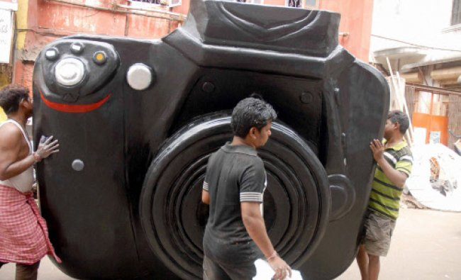 People shift a giant model of a Digital Camera made by an artist, at a studio in Kolkata on Monday.