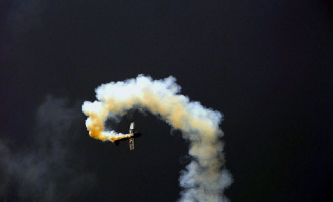 A plane leaves trail of fume during a fly-past display ahead of the 4th India Aviation 2014 show ...