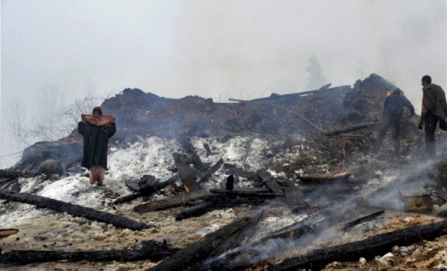 A woman stands beside the rubble of the house where two militants were killed in an encounter on Mo