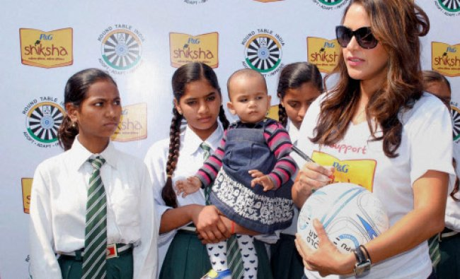 Neha Dhupia with school girls at a public meeting in Kanpur on Monday. PTI Photo