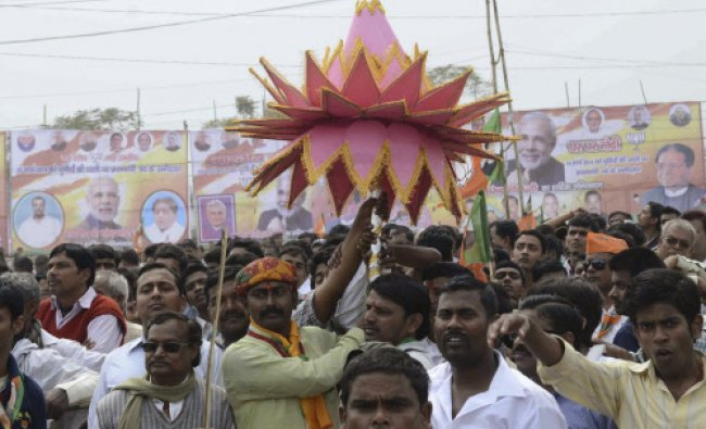 Supporters carry a paper made lotus, as Bharatiya Janata Partys (BJP) prime ministerial ...