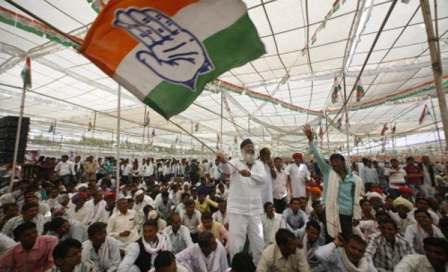 A man waves a Congress party flag at an election campaign rally addressed by party vice president...