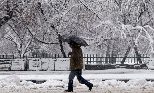 A man walks on a snow covered road during heavy snowfall in Srinagar on Tuesday...