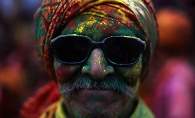 A man daubed in coloured powder poses for a picture at a temple during \'Lathmar Holi\'...