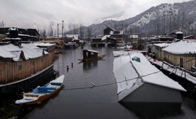 A shikarawalla rowing his boat near a houseboat capsized due to heavy snowfall...