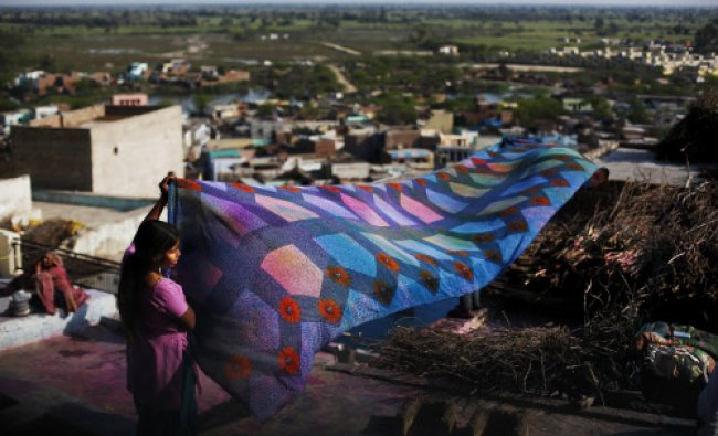 A girl spreads a sari on the roof of her house to let it dry during the Lathmar Holi festival...