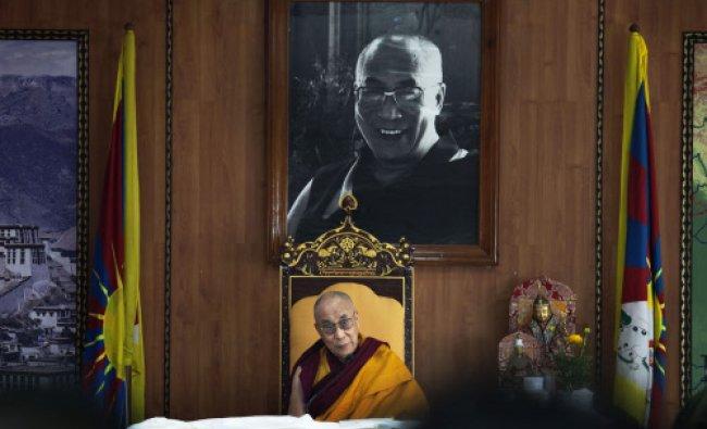 Tibetan spiritual leader the Dalai Lama sits beneath a photograph of himself before he addresses...
