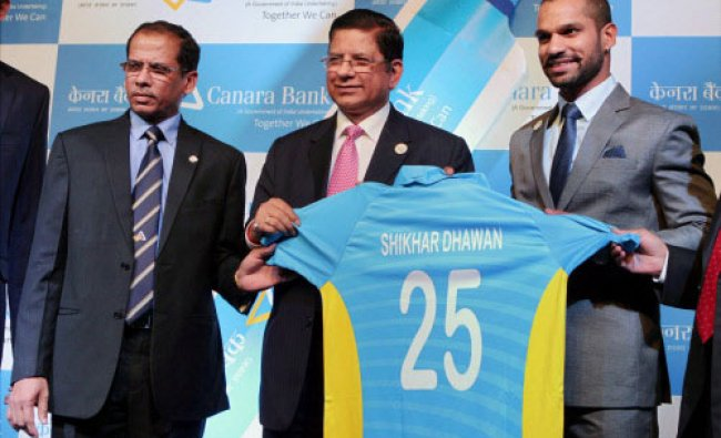 Cricketer Shikhar Dhawan poses with Canara Bank CMD R.K. Dubey after being announced ...