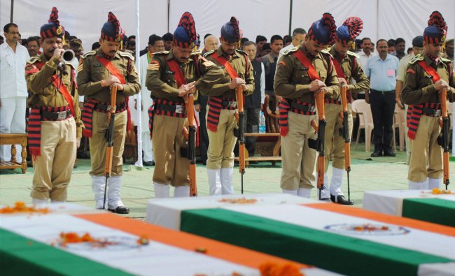 Security men paying tribute to the CRPF Jawans, killed in a Naxal attack, in Jagdalpur ...