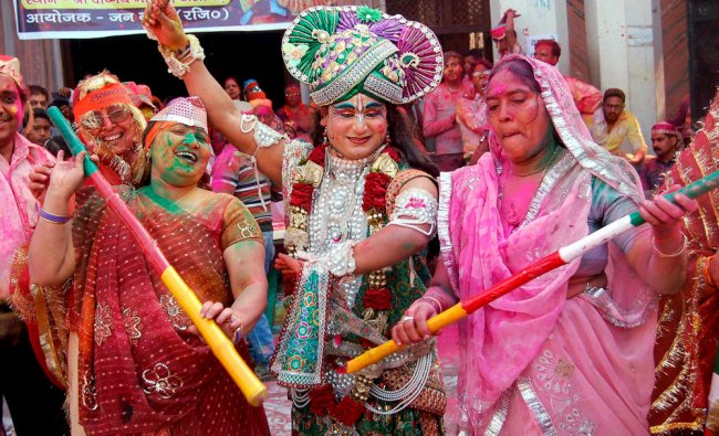 A Hindu devotee dressed up as Lord Krishna along with other devotees during a Holi celebration ...