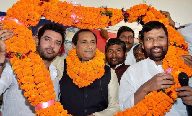 LJP chief Ram Vilas Paswan is garlanded with his son and party leader Chirag Paswan in Patna ...