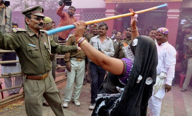 A Police officer participates in Latthmaar Holi celebration at Lord Krishna Janamsthan temple ...