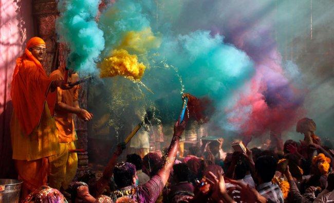Hindu priests throws coloured powder at the devotees during Holi celebrations in Vrindavan ...