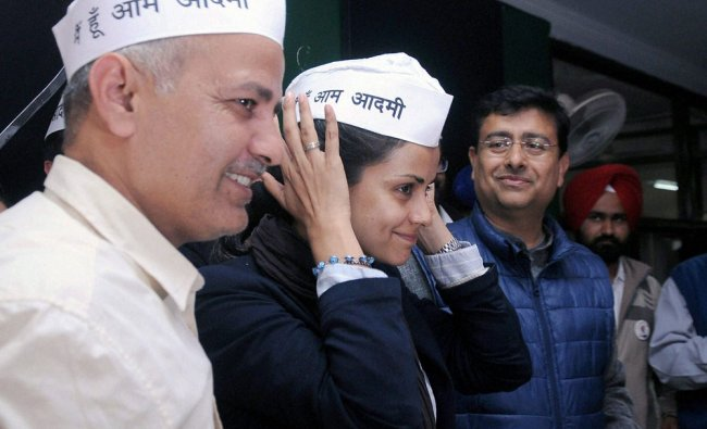 AAP leader Manish Sisodia looks on as actress Gul Panag adjusts her cap after joining the party ...