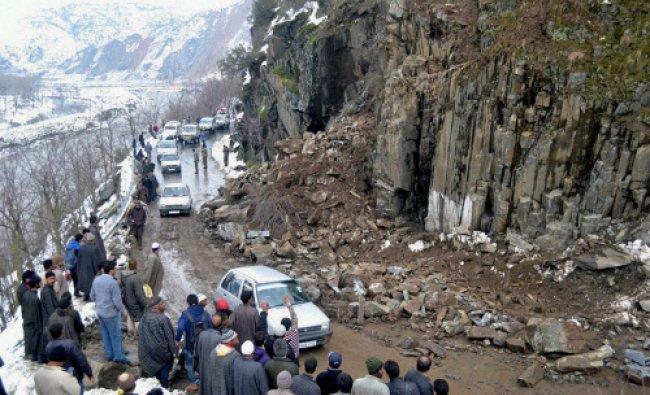 Locals clearing rubble from Srinagar-Muzaffarabad road after landslides in Jammu and Kashmir ...