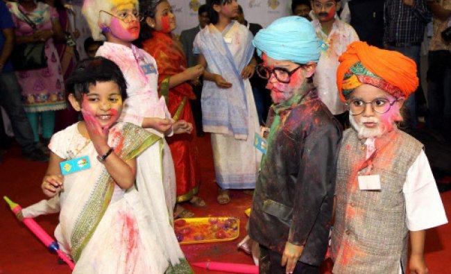 Children dress up as politicians celebrating Holi in Kolkata on Thursday. PTI Photo