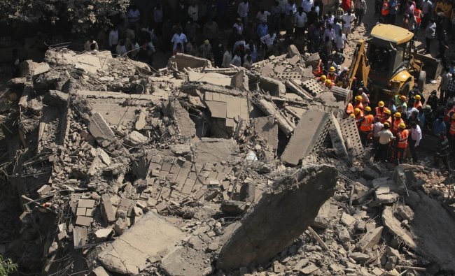 Rescue workers search for survivors in the debris of a building that collapsed in Mumbai ...