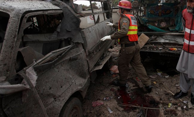 Rescue workers collect evidence at the site of a bomb blast on the outskirts of Peshawar ...