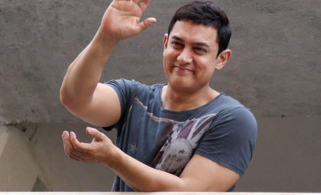 Aamir Khan waves at his fans gathered outside his house to wish the actor on his 49th birthday ...