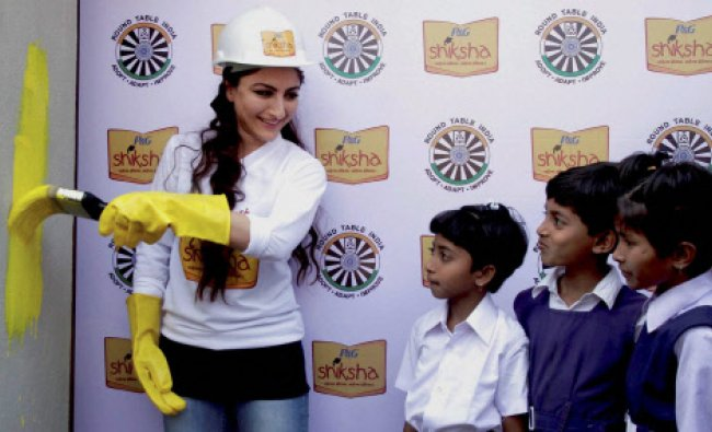 Bollywood actress Soha Ali Khan paints a wall with the school children in Hyderabad on Friday.