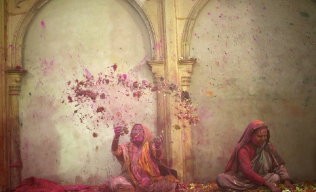 A widow throws flowers into the air during Holi celebrations organised by non-governmental...