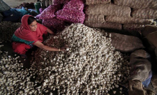 A worker sorts garlic at a wholesale market on the outskirts of Jammu...