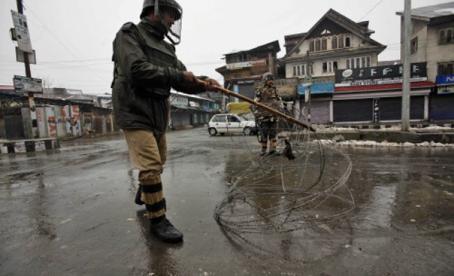 A paramilitary soldier adjusts barbed wire set up as road block on the day of curfew imposed...