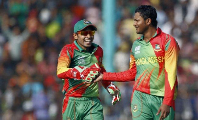 Bangladeshs Shakib Al Hasan, right, celebrates with Mushfiqur Rahim after taking the wicket...