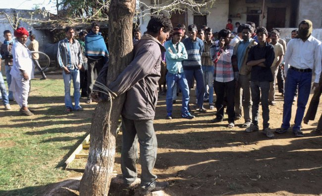 Villagers tie a thief with a tree to punish him in Beawar, Rajasthan on Saturday...