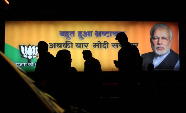 People walk past a billboard of BJP\'s PM candidate Narendra Modi at a Bus Stop in New Delhi ...