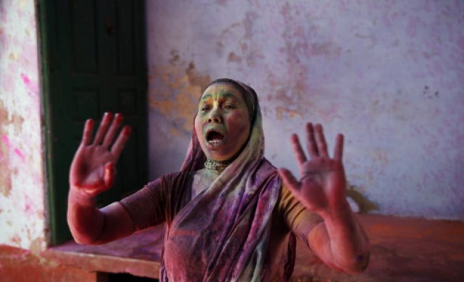 A widow reacts as others throw colored powder at her as a part of Holi celebrations at the Pagal...