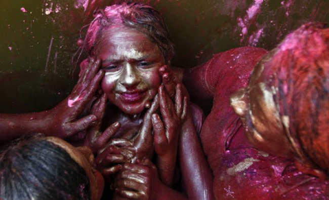 A girl reacts as other girls apply coloured paint on her face during Holi celebrations...