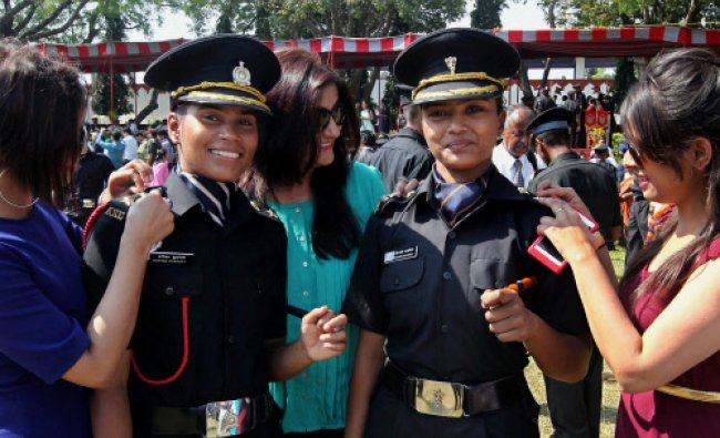 Family members having a look on the badges of two girl cadets after a passing out parade...