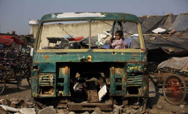 A boy watches from a broken windshield of an old lorry, or a small truck, in New Delhi...