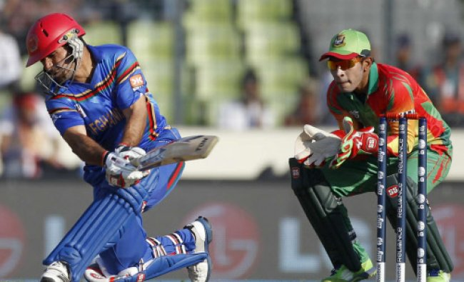 Afghanistan\'s captain Mohammad Nabi plays a ball as Bangladesh\'s captain and wicketkeeper...