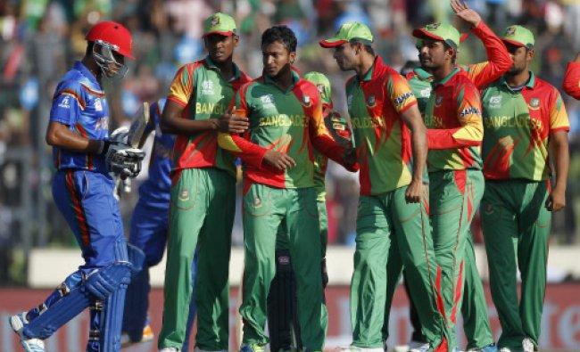 Afghanistan\'s Najeeb Tarakai (L) leaves the field as Bangladesh\'s fielders celebrate...