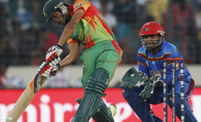 Bangladesh\'s Anamul Haque plays a ball as Afghanistan\'s wicketkeeper Mohammad Shahzad (R) watches...