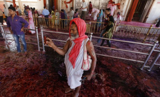 A Sadhu takes pictures with his mobile phone inside a temple during Holi celebrations ...