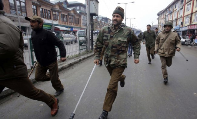 Policemen chase supporters of Jammu Kashmir Liberation Front (JKLF) during a protest in Srinagar...